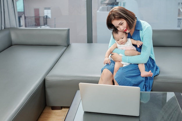 Souriante jeune femme vietnamienne avec bébé sur les tours vidéo appelant son parent, ami ou médecin