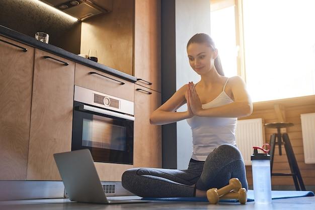 Souriante jeune femme yogi assise avec ses mains jointes sur la poitrine sur un tapis
