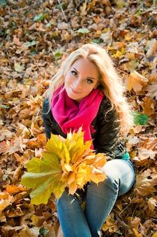 Souriante jeune fille allongée sur les feuilles d'érable d'automne à l'automne à l'extérieur