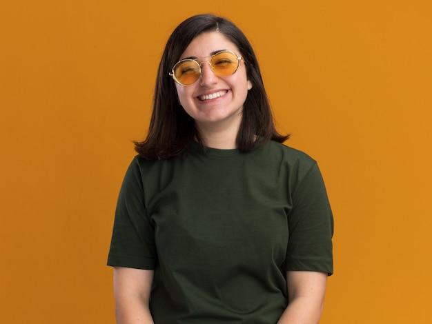 Souriante jeune fille assez caucasienne dans des lunettes de soleil regardant la caméra sur orange