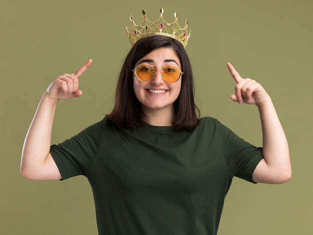 Souriante jeune fille assez caucasienne à lunettes de soleil avec couronne pointant vers le haut avec deux mains isolé sur mur vert olive avec espace copie