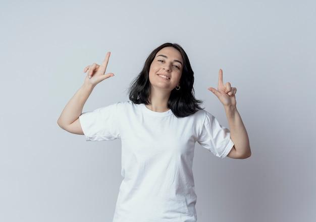 Souriante jeune fille assez caucasienne pointant avec les doigts vers le haut isolé sur fond blanc avec espace copie
