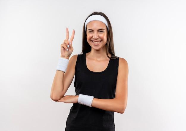 Souriante jeune fille assez sportive portant un bandeau et un bracelet clignotant et faisant le geste de paix sur l'espace blanc