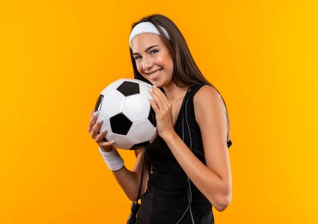 Souriante jeune fille assez sportive portant bandeau et bracelet tenant un ballon de football avec une corde à sauter autour de son cou isolé sur l'espace orange