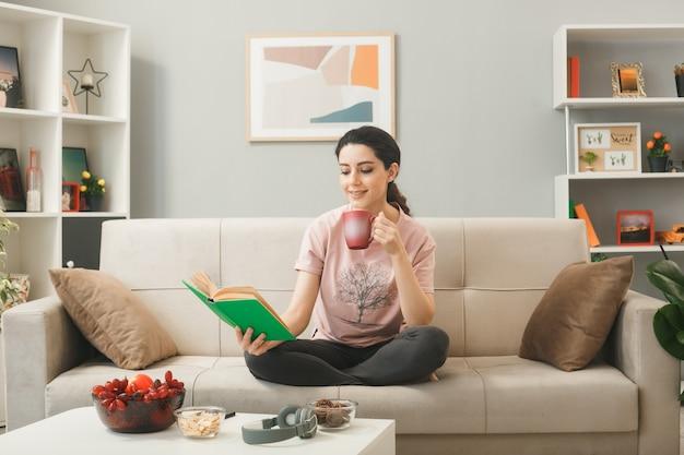 Souriante jeune fille assise sur un canapé lisant un livre tenant une tasse de thé derrière une table basse dans le salon