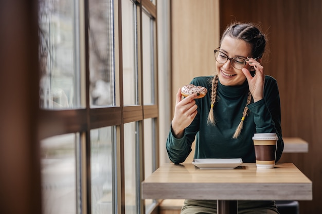 Souriante jeune fille assise à la pâtisserie, tenant un beignet et en le regardant. quelle délicieuse menace.