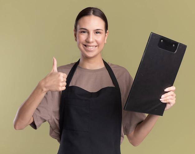 Souriante jeune fille de barbier brune en uniforme les pouces vers le haut et détient le presse-papiers