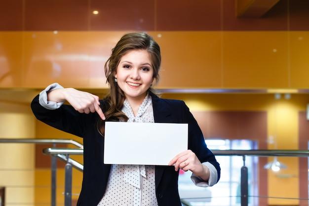 Souriante jeune fille belle montre sur une carte blanche vierge