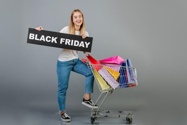 Souriante jeune fille belle avec signe noir vendredi et poussette plein de sacs colorés