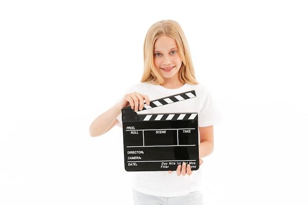 Souriante jeune fille blonde dans des vêtements décontractés tenant le film faisant clap sur blanc
