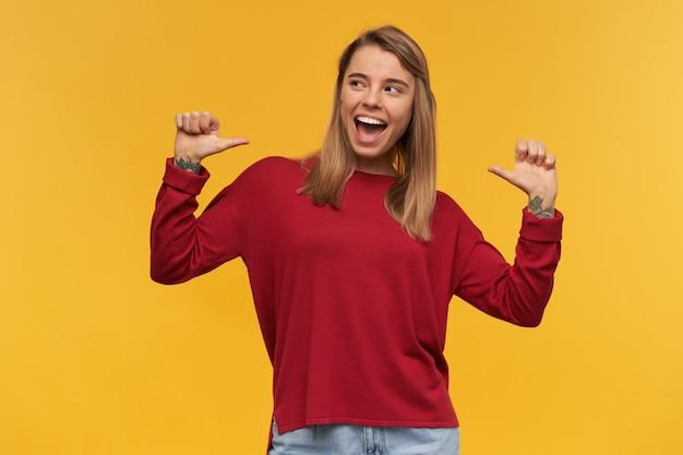 Souriante jeune fille blonde, heureuse, pointant avec les pouces sur elle-même, regardant vers le côté gauche