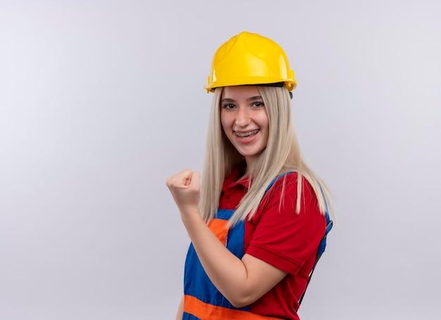 Souriante jeune fille blonde ingénieur constructeur en uniforme dans un appareil dentaire en levant le poing sur un espace blanc isolé avec copie espace