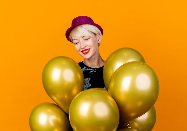 Souriante jeune fille blonde portant un chapeau de fête debout derrière des ballons en les regardant isolés sur fond orange