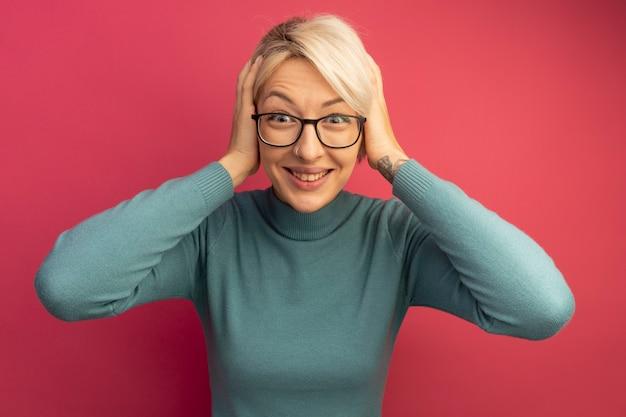 Souriante jeune fille blonde portant des lunettes regardant en gardant les mains sur la tête isolées sur le mur rose
