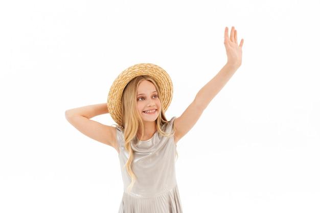 Souriante jeune fille blonde en robe et chapeau de paille en agitant et en détournant les yeux sur blanc