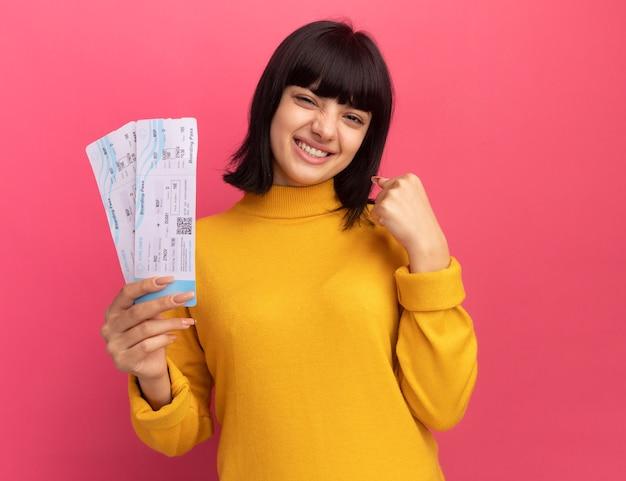Souriante jeune fille brune caucasienne garde le poing et détient des billets d'avion isolés sur un mur rose avec espace de copie