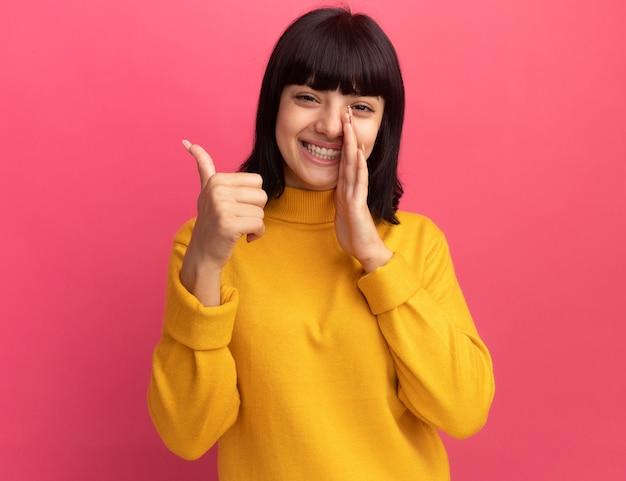 Souriante jeune fille brune caucasienne tient la main près de la bouche et les pouces vers le haut sur rose