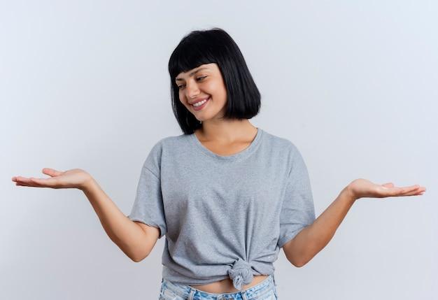 Souriante jeune fille brune caucasienne tient les mains ouvertes en regardant sur le côté