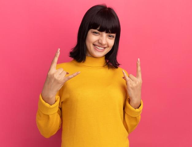 Souriante jeune fille caucasienne brune gestes cornes signe avec deux mains