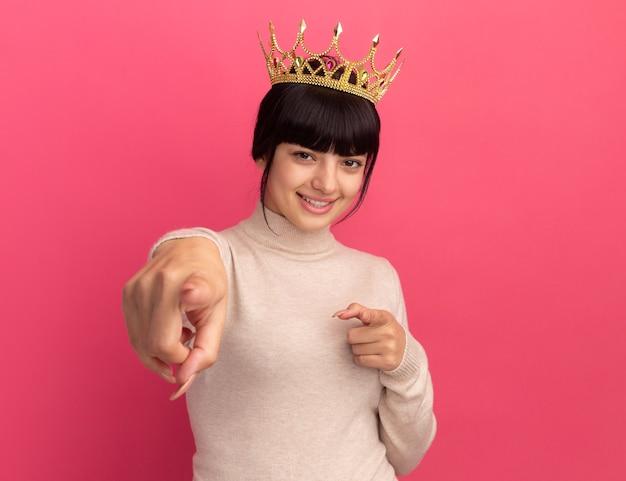 Souriante jeune fille caucasienne brune avec des points de couronne avec deux mains isolées sur un mur rose avec espace de copie