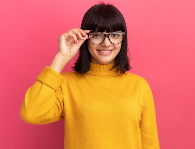 Souriante jeune fille caucasienne brune regarde la caméra à travers des lunettes optiques