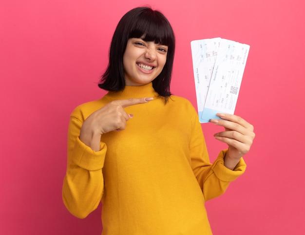 Souriante jeune fille caucasienne brune tient et pointe les billets d'avion