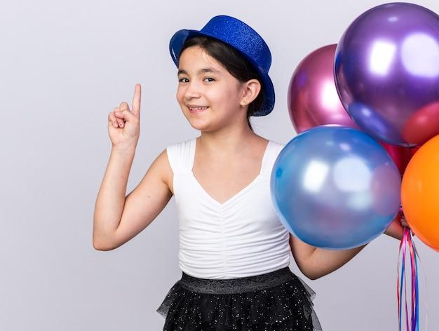Souriante jeune fille caucasienne avec chapeau de fête bleu tenant des ballons à l'hélium et pointant vers le haut isolé sur mur blanc avec espace de copie