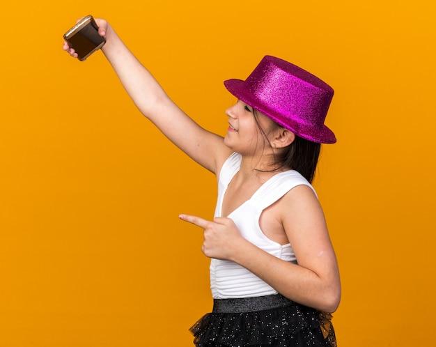 Souriante jeune fille caucasienne avec chapeau de fête violet pointant sur le téléphone prenant selfie isolé sur mur orange avec espace de copie