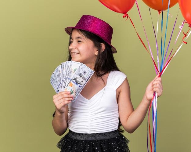 Souriante jeune fille caucasienne avec chapeau de fête violet tenant de l'argent et des ballons à l'hélium regardant le côté isolé sur un mur vert olive avec espace de copie