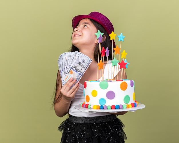 Souriante jeune fille caucasienne avec chapeau de fête violet tenant un gâteau d'anniversaire et de l'argent regardant le côté isolé sur un mur vert olive avec espace de copie