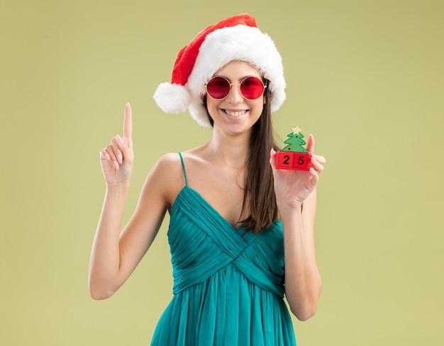 Souriante jeune fille caucasienne dans des lunettes de soleil avec bonnet de noel tenant ornement d'arbre de noël et pointant vers le haut