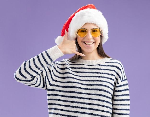 Souriante jeune fille caucasienne à lunettes de soleil avec bonnet de noel gesticulant appelez-moi signe de la main isolé sur mur violet avec espace de copie