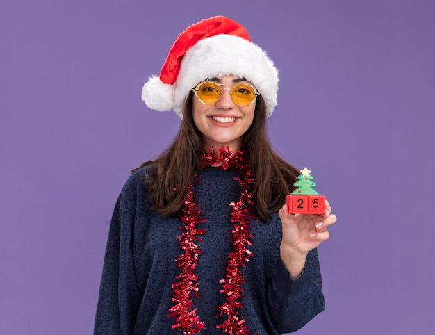 Souriante jeune fille caucasienne à lunettes de soleil avec bonnet de noel et guirlande autour du cou détient un ornement d'arbre de noël isolé sur un mur violet avec espace de copie