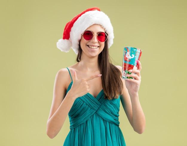Souriante jeune fille caucasienne à lunettes de soleil avec bonnet de noel tenant et pointant sur la tasse de papier