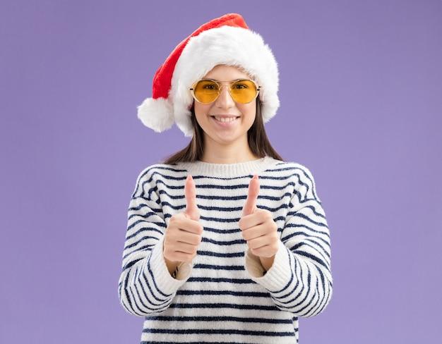 Souriante jeune fille caucasienne à lunettes de soleil avec chapeau de père noël pouces vers le haut