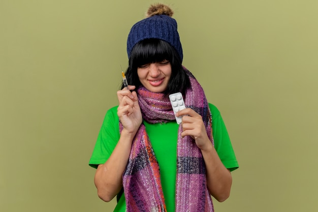 Souriante jeune fille caucasienne malade portant chapeau d'hiver et écharpe tenant la seringue et le paquet de comprimés médicaux avec les yeux fermés isolé sur fond vert olive avec espace copie