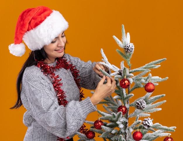 Souriante jeune fille caucasienne portant chapeau de noël et guirlande de guirlandes autour du cou debout en vue de profil près de sapin de noël en le regardant décorer isolé sur fond orange