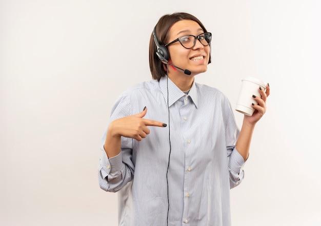 Souriante jeune fille de centre d'appels portant des lunettes et un casque tenant et pointant sur une tasse de café en plastique isolé sur un mur blanc