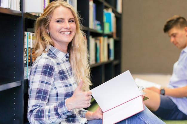 Souriante jeune fille dans la bibliothèque