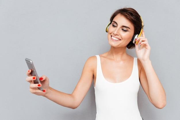 Souriante jeune fille écoutant de la musique sur smartphone avec un casque sur fond gris