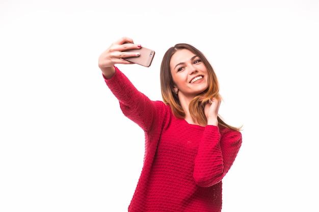 Souriante jeune fille faisant selfie photo sur smartphone isolé sur mur gris