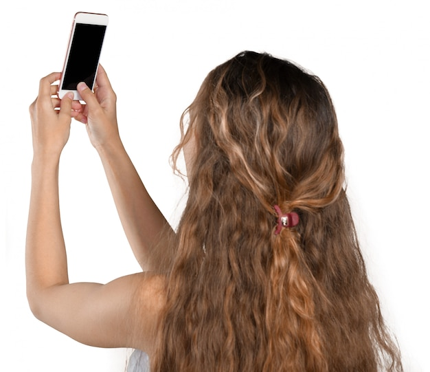 Souriante jeune fille faisant selfie photo sur smartphone