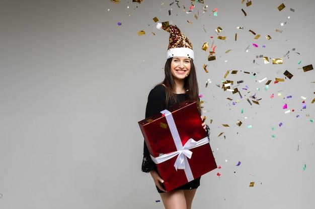 Souriante jeune fille avec un grand cadeau festif pointant à la main sur un espace vide avec des confettis de vacances sur fond gris