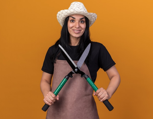 Souriante jeune fille de jardinier en uniforme et chapeau tenant des cisailles à haie regardant l'avant isolé sur un mur orange