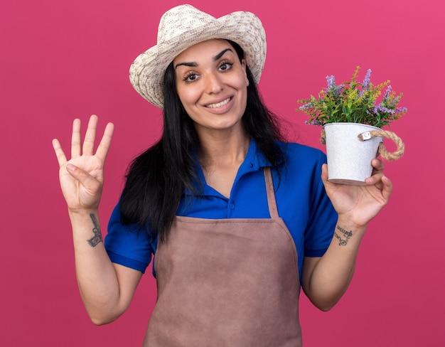 Souriante jeune fille jardinière caucasienne en uniforme et chapeau tenant un pot de fleurs montrant quatre avec la main isolée sur le mur rose