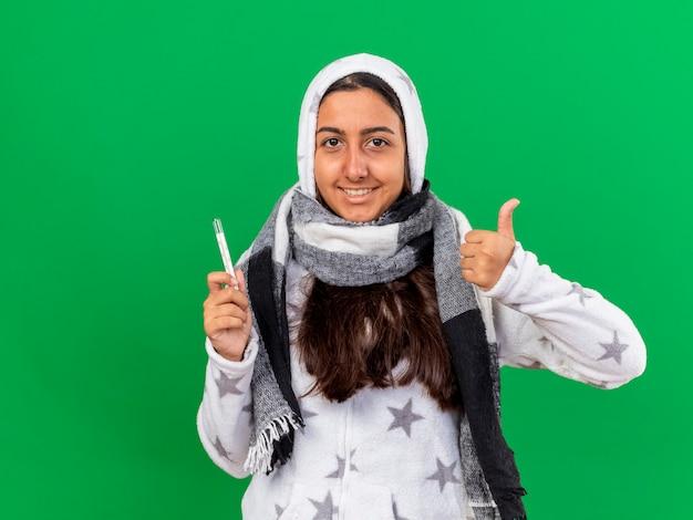 Souriante jeune fille malade mettant sur capuche wearin écharpe tenant thermomètre montrant le pouce vers le haut isolé sur vert