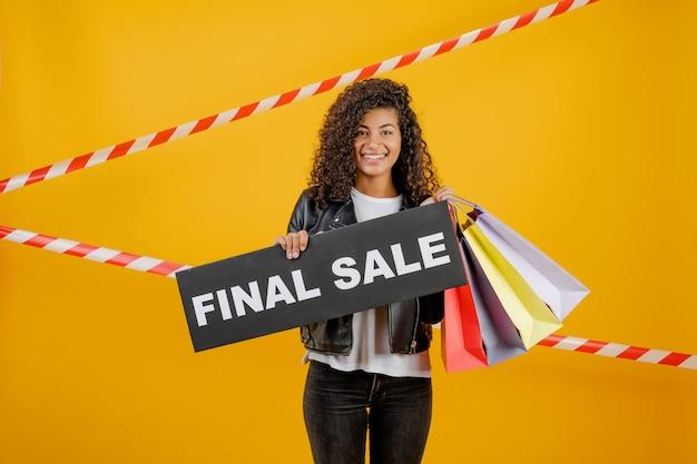 Souriante jeune fille noire avec signe de vente finale et sacs colorés isolés sur jaune avec du ruban de signalisation