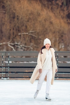 Souriante jeune fille patinant sur la patinoire à l'extérieur