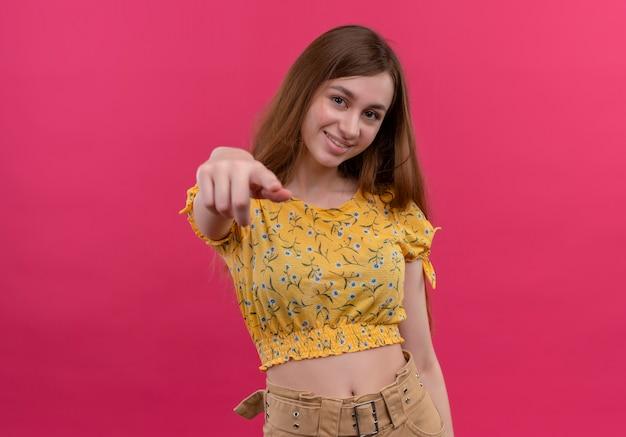 Souriante jeune fille pointant sur un mur rose isolé avec espace copie