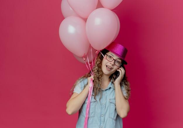 Souriante Jeune Fille Portant Des Lunettes Et Un Chapeau Rose Tenant Des Ballons Et Parle Au Téléphone Isolé Sur Rose Photo gratuit